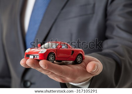 Unrecognizable businessman showing a toy car on his palm