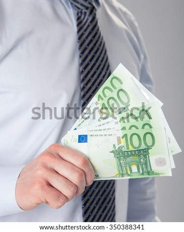 Unrecognizable businessman showing euro banknotes