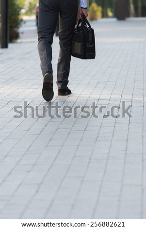 Unrecognizable businessman walking on the street near office building - stock photo