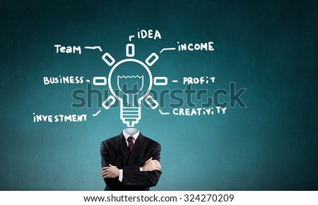 Unrecognizable businessman with business sketches instead of head on blue background - stock photo