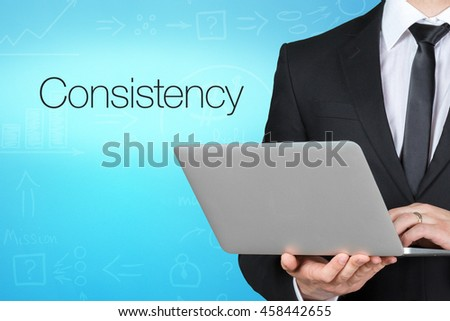 Unrecognizable businessman with laptop standing near text - Consistency - stock photo