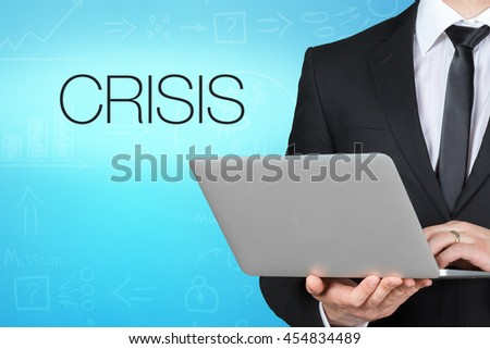 Unrecognizable businessman with laptop standing near text - crisis - stock photo