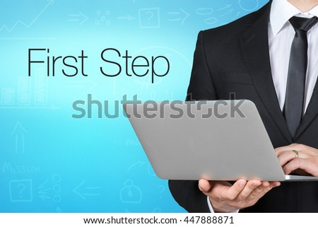 Unrecognizable businessman with laptop standing near text - first step - stock photo