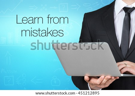"Unrecognizable businessman with laptop standing near text ""Learn from mistakes"" - stock photo"