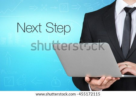 Unrecognizable businessman with laptop standing near text - next step  - stock photo