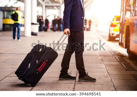 Unrecognizable businessman with luggage at the airport, entering - stock photo