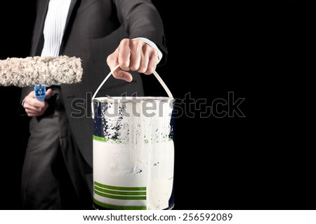 Unrecognizable businessman with suit holding paint roller and a bucket of paint - stock photo