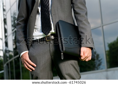 Unrecognizable businessman with suitcase close-up on a modern building background - stock photo