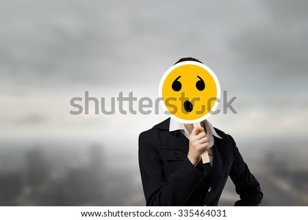 Unrecognizable businesswoman hiding her face behind sad mask - stock photo