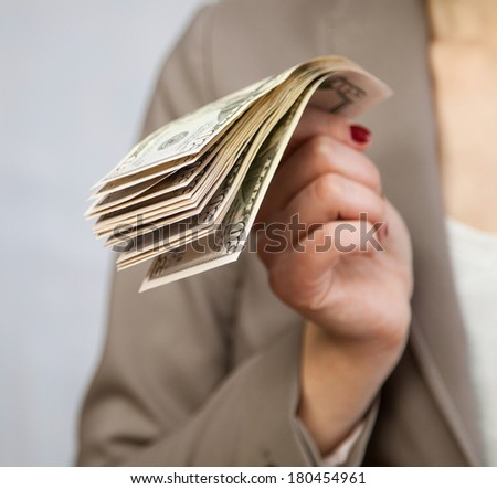 Unrecognizable businesswoman holding dollars, neutral background - stock photo