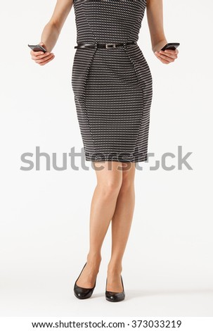 Unrecognizable businesswoman  holding two cellphones , white background - stock photo
