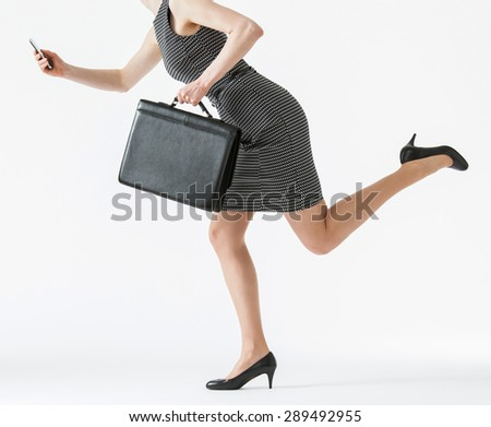 Unrecognizable businesswoman running and holding her cellphone and a briefcase, white background - stock photo