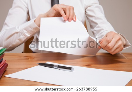 Unrecognizable businesswoman tears sheet of paper - stock photo