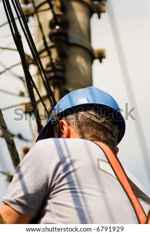 Unrecognizable bust of utility worker (from behind) with electrical cables in the background. - stock photo