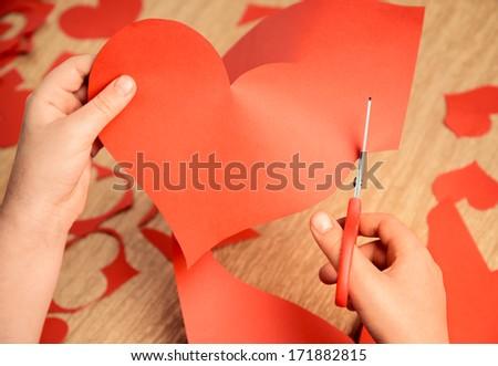 Unrecognizable child cuts a red paper heart - stock photo