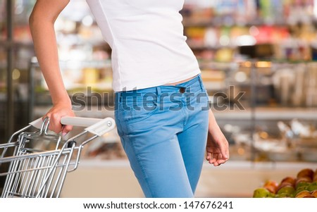 Unrecognizable female customer shopping at supermarket with trolley