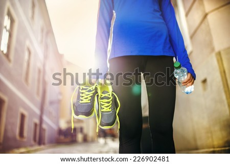 Unrecognizable female runner carrying her running shoes and bottle of water in old city center - stock photo
