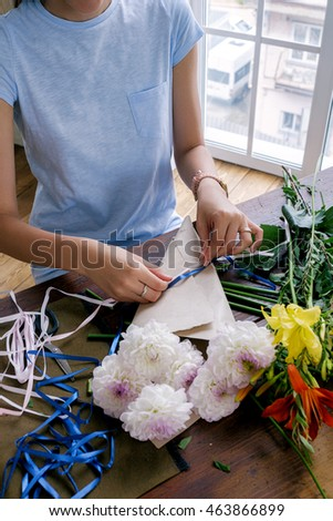 Unrecognizable florist in blue t-shirt tying ropes on bouquet
