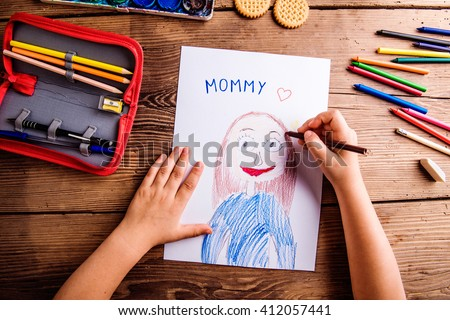 Unrecognizable girl drawing picture of her mother. Wooden backgr - stock photo