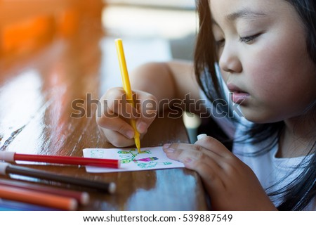 Unrecognizable girl drawing pictures of her mother and father.
