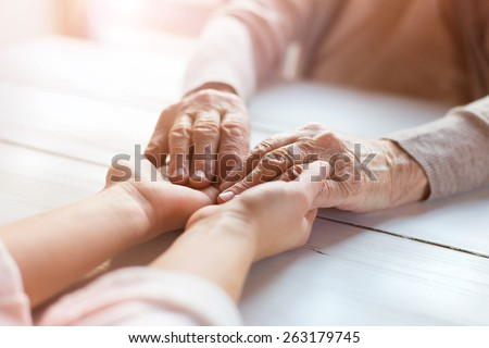 Unrecognizable grandmother and her granddaughter holding hands. - stock photo