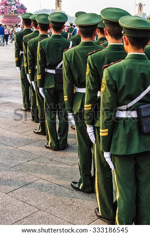 Unrecognizable group of soldiers standing in line and seen from behind. Wearing uniforms including caps. The soldiers belong to the Chinese armed forces. - stock photo