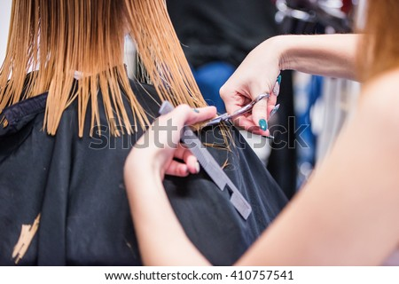 Unrecognizable hairdresser cutting hair of her beautiful young c - stock photo