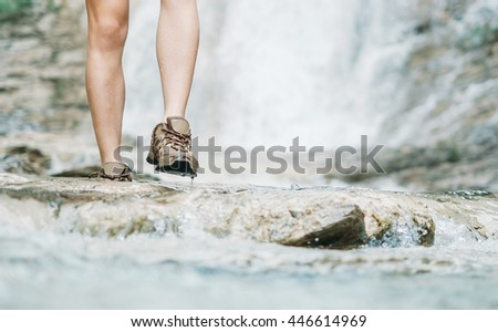 Unrecognizable hiker young woman walking along mountain river in summer outdoor, view of legs, close-up