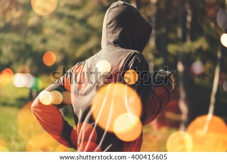 Unrecognizable hooded man jogging outdoors, healthy lifestyle activity in the park in early autumn morning, retro toned image with selective focus and bokeh light - stock photo