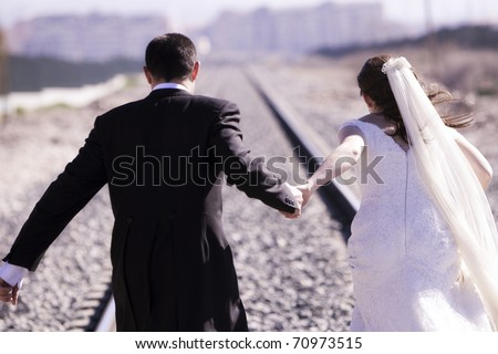 Unrecognizable just married couple running away - stock photo