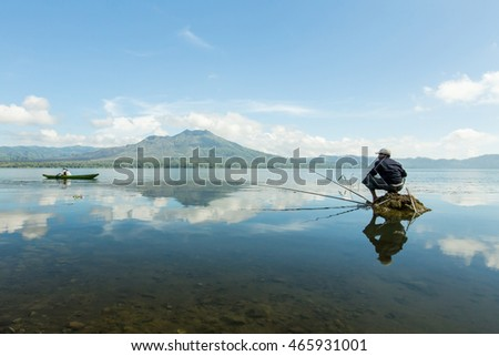 Unrecognizable lone man fishing in the middle of the Lake Batur overlooking Mount Batur during cloudy blue sky in Bali Indonesia.