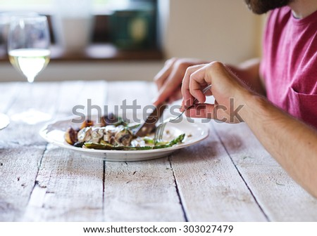 Unrecognizable man holding fork and knife cutting food on a plate - stock photo