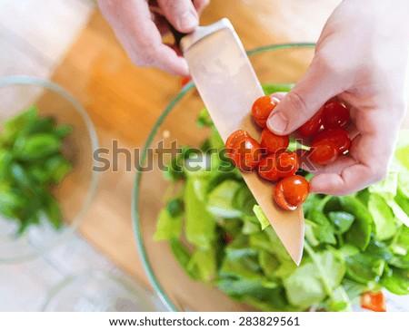Unrecognizable man preparing colorful vegetable salad - stock photo