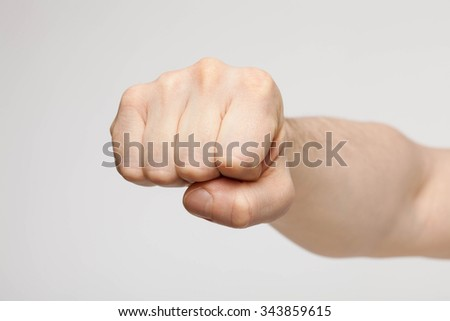 Unrecognizable man showing a strong fist, neutral background - stock photo