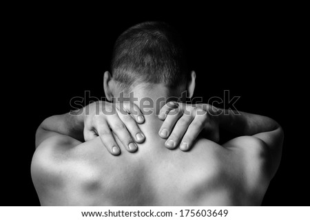 Unrecognizable man touches neck, pain in the neck, rear view - stock photo