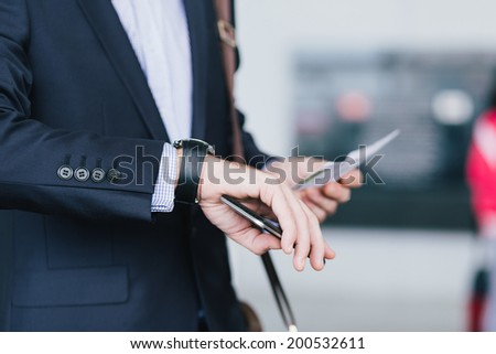 Unrecognizable manager with a cellphone and airplane ticket checking time on his watch - stock photo