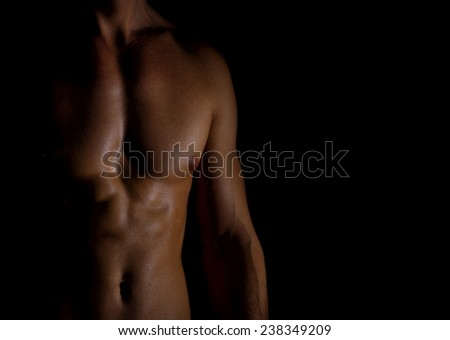 Unrecognizable muscular male body on black background. - stock photo