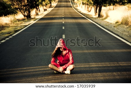 Unrecognizable mystery woman in the middle of the road. - stock photo