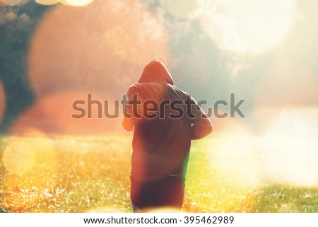 Unrecognizable ordinary hooded man jogging outdoors, healthy lifestyle activity in the park in early autumn morning, retro toned image with selective focus and bokeh light - stock photo