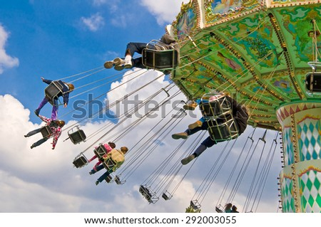unrecognizable people on flying swing attraction - stock photo