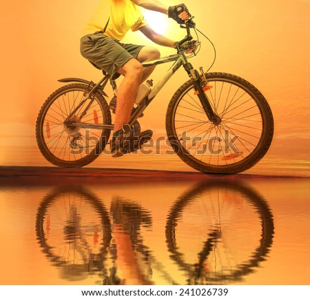 Unrecognizable person No face Mountain Biker on sky with clouds background Man wear yellow sport shirt gray snickers and shorts Empty copy space for inscription Reflection sun on yellow water texture  - stock photo