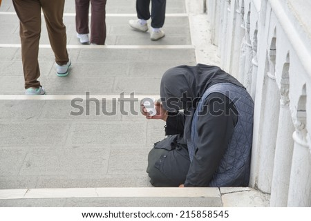 Unrecognizable person No face The poor woman sitting on the fence in perspective and asks for money on legs background - stock photo