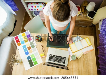 Unrecognizable pregnant woman in home office with digital tablet and pen - stock photo