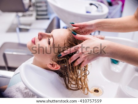 Unrecognizable professional hairdresser washing hair to her clie - stock photo