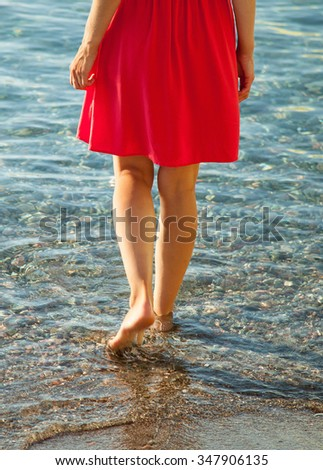 Unrecognizable slender girl walking near the seashore in limpid water