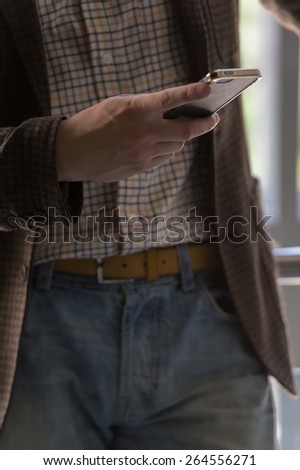 Unrecognizable stylish businessman texting on the phone in office - stock photo