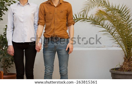 unrecognizable trendy young couple holding hands outdoors - stock photo