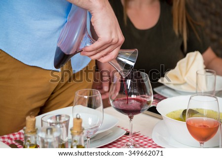 Unrecognizable waiter pouring red wine into wineglass during lunch in a restaurant. - stock photo
