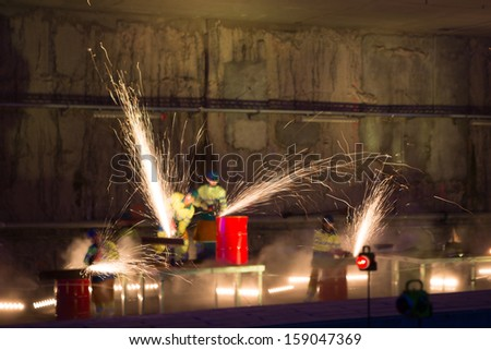 Unrecognizable Welders in action with bright sparks during the opening show of Diabolo Line, the direct train connexion between Brussels Airport and the center of the capital of Europe. - stock photo