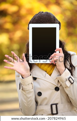 Unrecognizable woman covering her face with digital tablet blank screen and waving in autumn season. Hidden female holding touchpad frame for copy space message or information. - stock photo